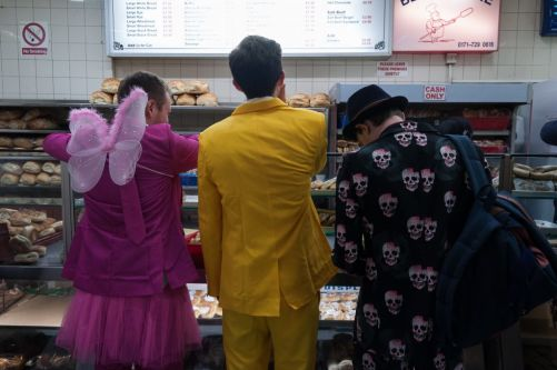 three people in fancy dress at a food counter