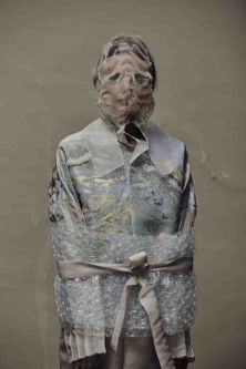 A model is wrapped in bubblewrap and pastel-coloured materials.