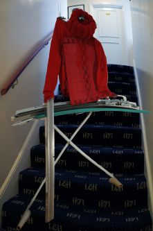 Handcrafted mannequin on staircase wearing a red knitted top.