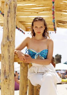 Woman in a beach shack wearing the Poppy bandana scarf as a bikini top