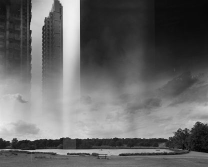 Black and white image of a skyscraper and park with a lake