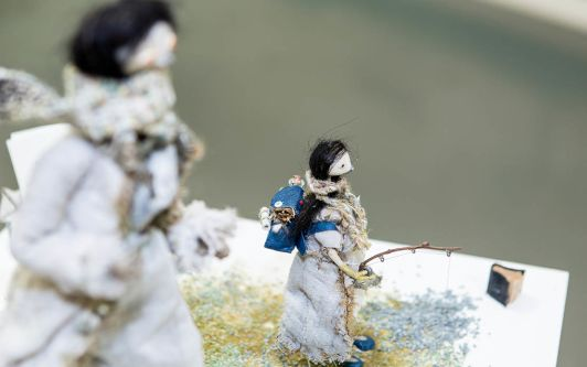 A handcrafted figure, it appears to be female, wearing a scarf made of string and is holding a fishing rod in a snow setting.