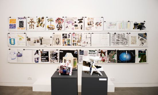 A large wall display of examples of sketches, drawings and collages taken from sketchbooks.
