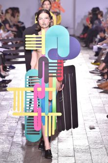 A model walking down a catwalk wearing a garment made from abstract shapes of varying size and colours