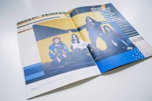 Double-spread in a magazine. Showing four people posing in front of a yellow wall.