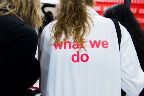 image of the back of a student wearing white overall reading