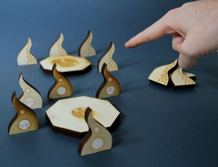 image of game made out of 3d wooden pieces which are displayed on a table. there is hand pointing to the game