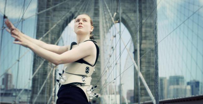 A woman playing the Human Hard on the Brooklyn Bridge