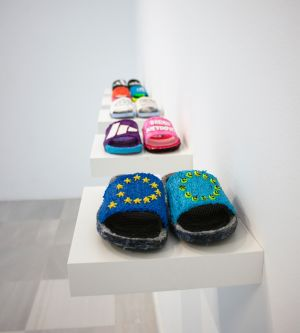 Handmade slippers are on display. The first pair have the EU symbol on it