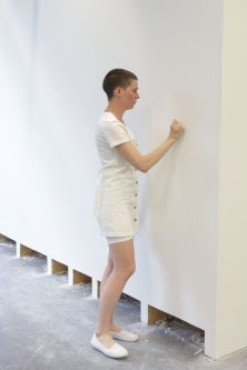Woman in white writing on white wall