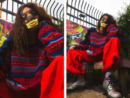 Female model wearing blue and yellow knitted mask and blue and red knitted jumper and red trousers