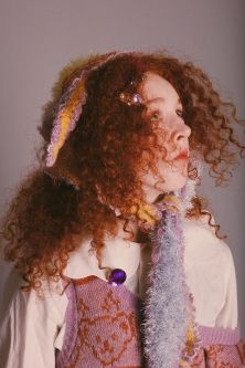 Female model with red curly hair wearing lilac jumper with teddy bear motif