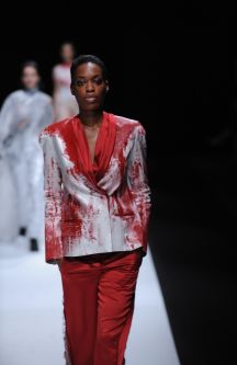 Female model wearing red and silver suit designed by Kang An