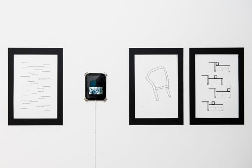 Three images hung on a wall next to a tablet device.