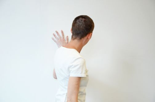 A person wearing a white t-shirt facing a white wall and touching it
