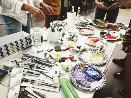 Students stood around a table filled with paint brushes and paints.