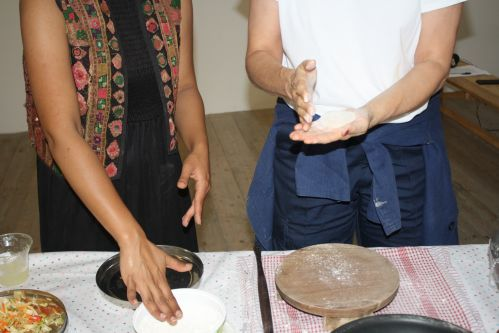 close up of two people making roti
