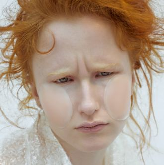 Model frowning, with very orange hair and no eyebrows