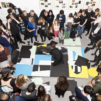 Photograph of a crowd of people viewing a large artwork on the gallery floor