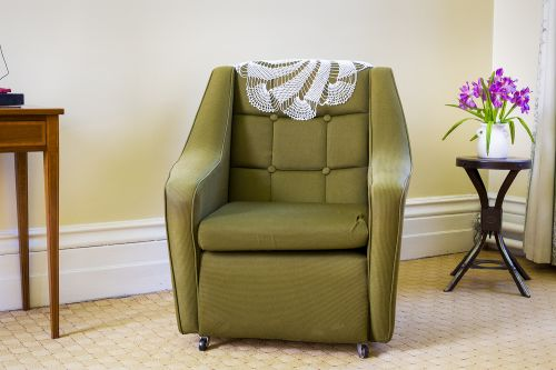 Photograph of a green leather chair in an interior.