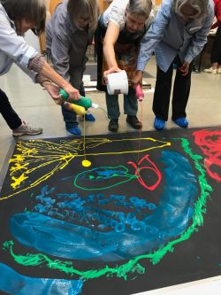 Four people pouring coloured paint onto large black canvas