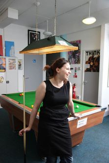 Photo of a female student leaning against a snooker table in Cordwainers Court communal area