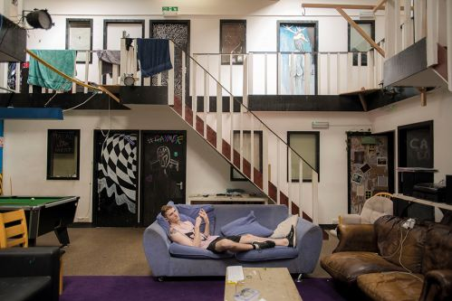 Man lying on a purple sofa in the middle of a two-level loft apartment with stairs in the background