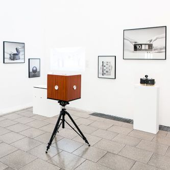 Installation view with free-standing camera and wall mounted photographs of work by Lam Pok Yin & Jeff Chong Ng.