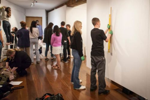 Students installing artworks in a gallery space