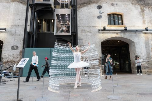 A person dancing next to lots of rows of glasses