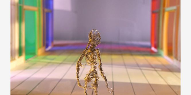 film still of human figure made out of metal wire whilst standing in multicoloured shopping centre