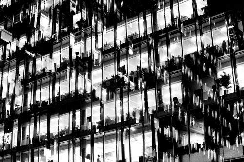 Blurry abstract black and white photo of external glass windows on tower block.