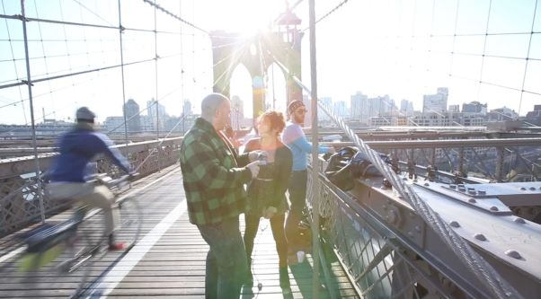 Di on Brooklyn Bridge with a cyclist riding past