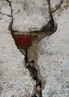 Close-up of red detailing in a crack in a concrete wall