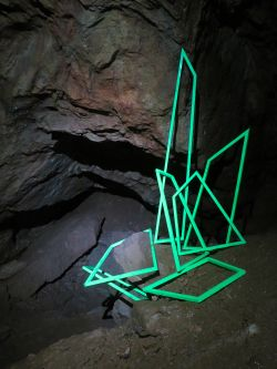Green linear sculptures in a cave