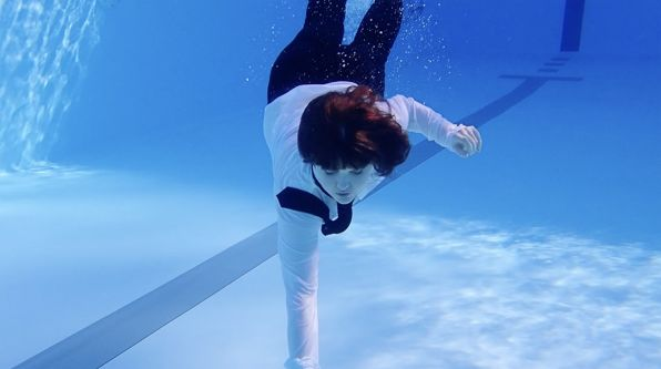 A person wearing a suit swimming underwater
