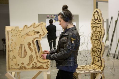 Woman playing on wooden interactive sculpture