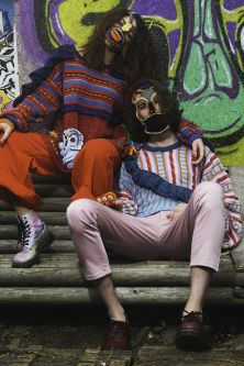 Female model wearing blue and yellow knitted mask with blue and red knitted jumper, leaning on a male model wearing grey and black knitted mask with a pink and blue knitted jumper in front of graffiti