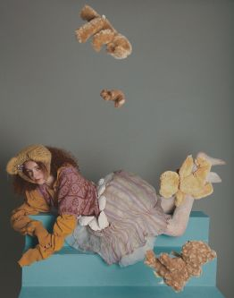 Female model with red curly hair wearing teddy bear knitted hat and lilac jumper dress with teddy bear motif lying down with teddy bears falling from the sky