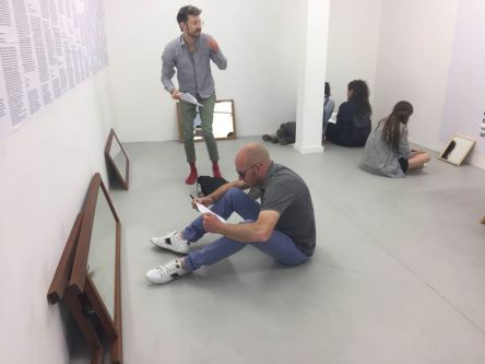 gallery installation with mirrors proped against walls and people sittin gon floor looking at themselves in the mirrors