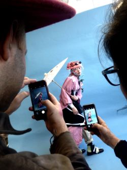 Students taking a photo of a female model in a pink outfit against a blue background
