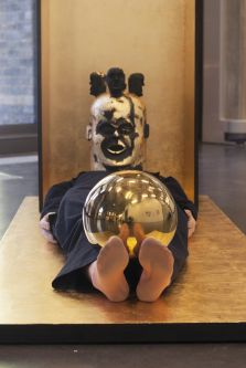 A person lying down wearing a painted mask with three heads attached to the top while balancing a gold reflective orb on their feet