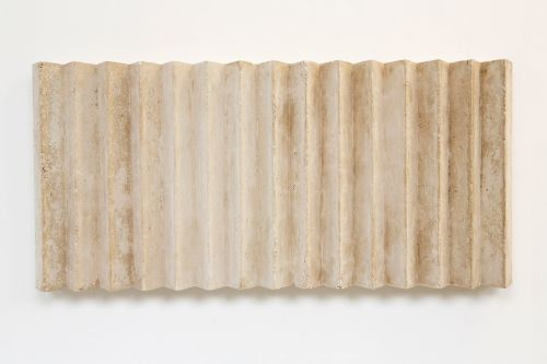 Concrete sculpture piece mounted on gallery wall by Lauren Allen.