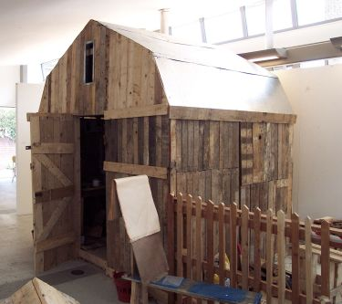Wooden shed construction in gallery by Jon Griffiths.