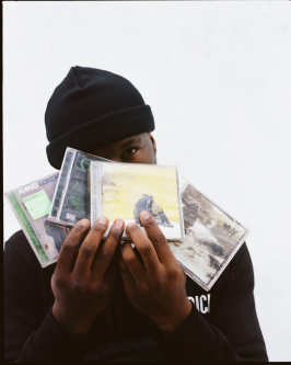 Close up shot of a guy holding 4 Grime music CDs