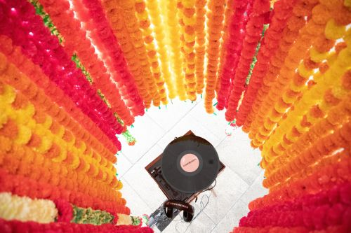 Colourful flowers dropped from the ceiling in the shape of a circle with record player in the middle.