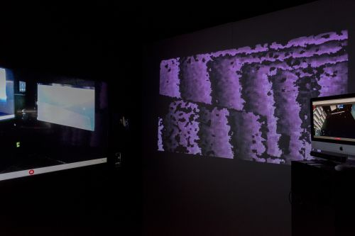 Computer screens and a purple digital projection.