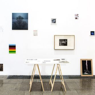 Installation view of multicoloured photos on the wall and gallery tables