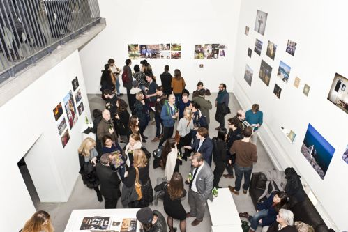 Crowd of people in a gallery viewing a photography exhibition