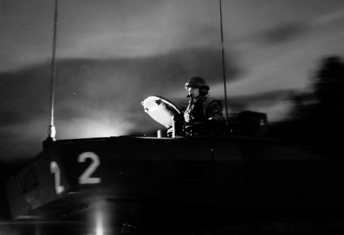 Black and white photograph of a soldier emerging from a tank.